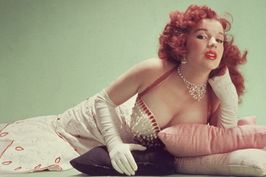 circa 1955:  Studio portrait of Blaze Starr, reclining on pillows on the floor, wearing a red-trimmed white dress and white elbow-length gloves.  (Photo by Hulton Archive/Getty Images)